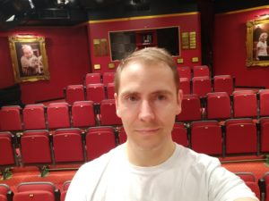 A selfie taken with the window into a technical booth at the very back, behind rows of theatre seats
