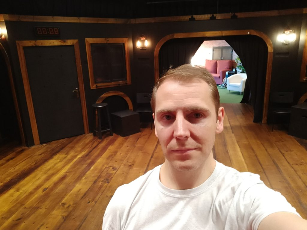A selfie taken in front of a wooden stage with several doors and entrances built in to it